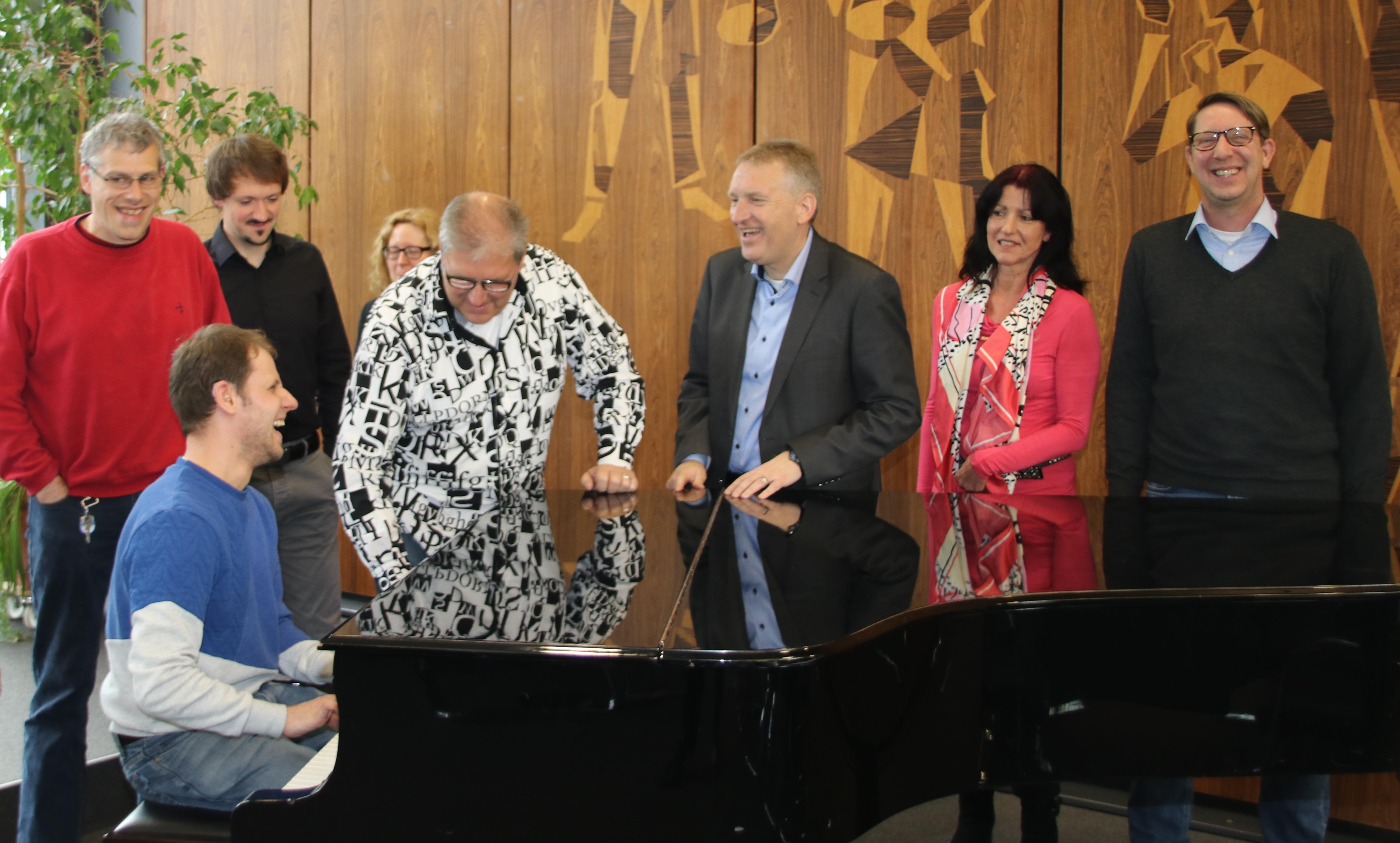 Bei der Pressemitteilung wird spontan ein Lied gesungen und am Klavier begleitet.