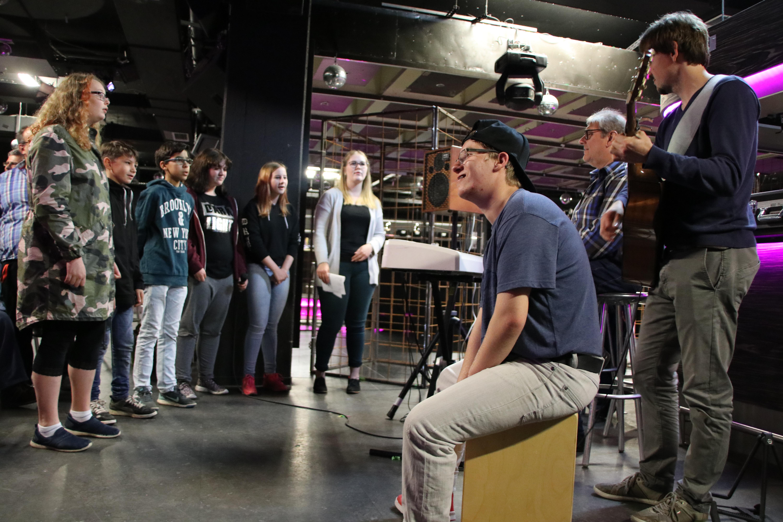 mehrere Schüler und Schülerinnen singen gemeinsam zu Keybord und Gitarre